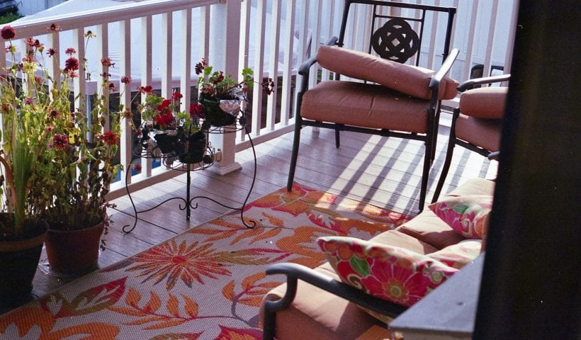 Balcony with chairs, plants and a rug
